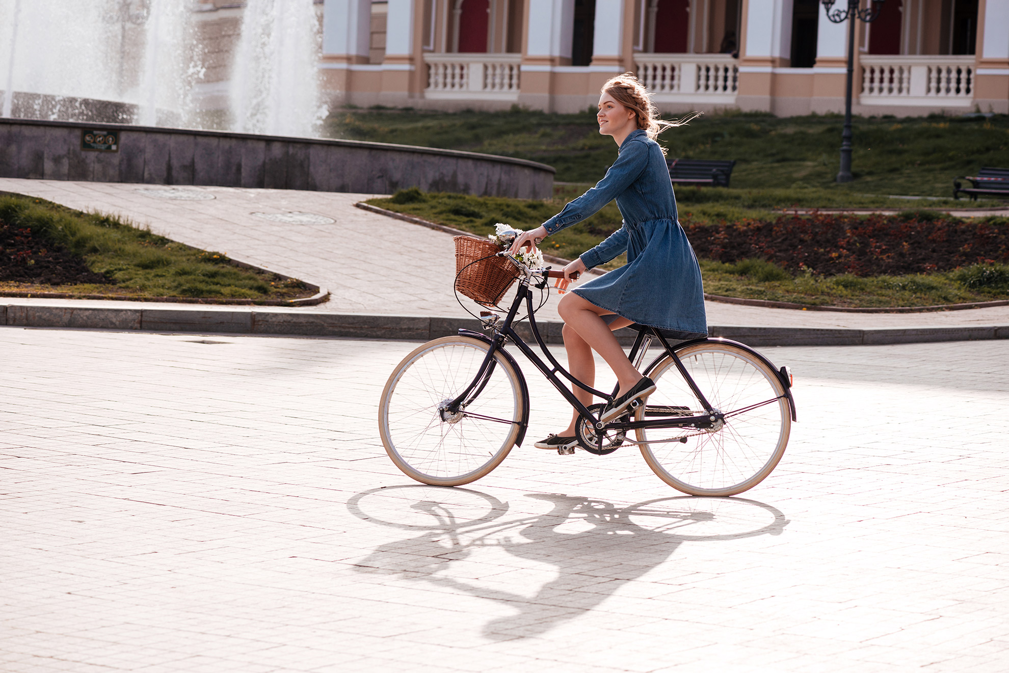 Kobieta w sukience na rowerze, ilustracja do artykułu w którym odpowiadamy, czy da się jeździć w sukience na rowerze