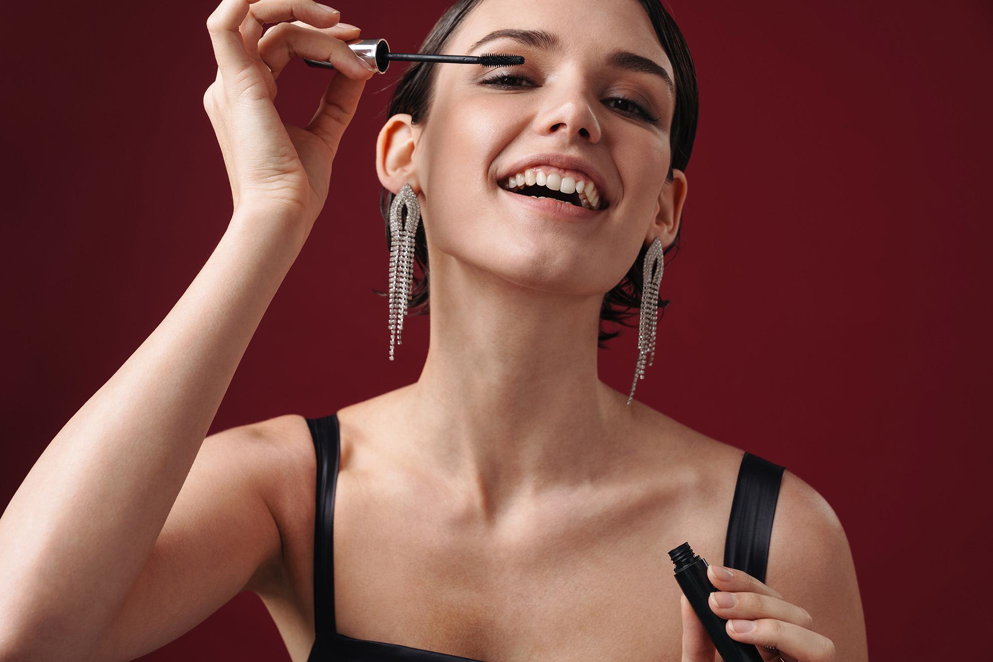 Kobieta robiąca makijaż, ilustracja do artykułu o makijażu do bordowej sukienki