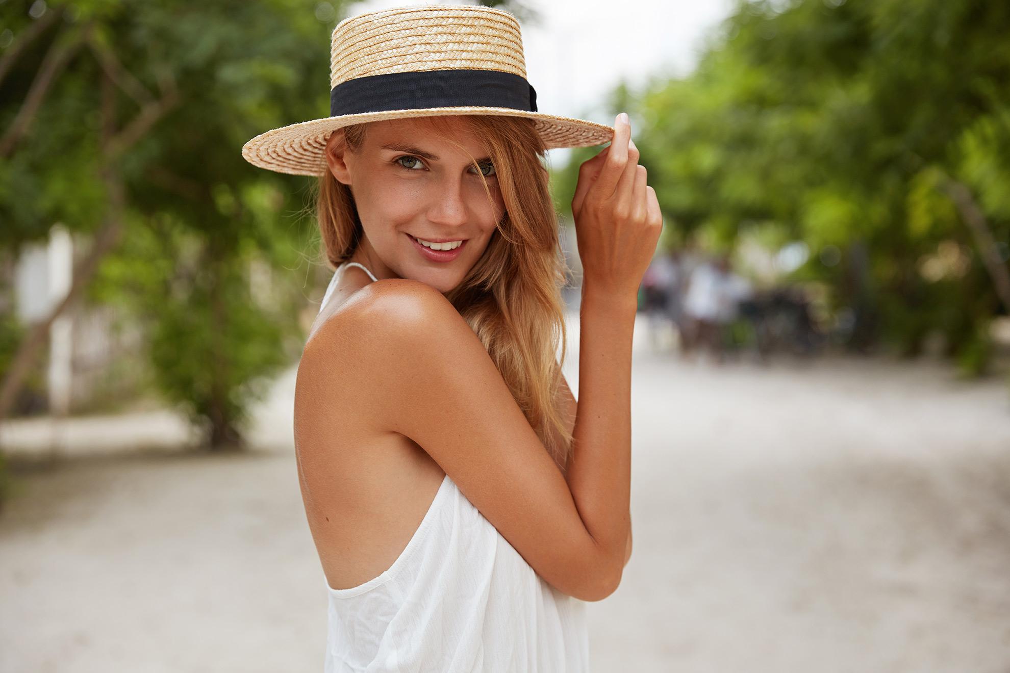 Kobieta w białej sukience i kapeluszu, ilustracja do artykułu o hitowych sukienkach